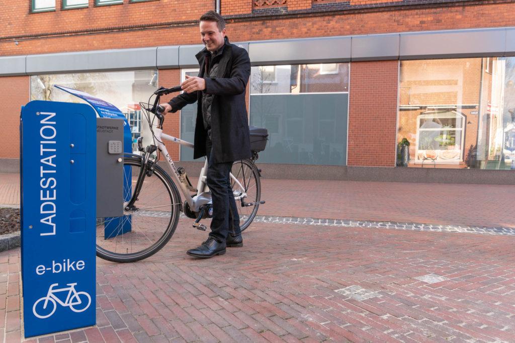 E-Bike-Fahrende können den Akku ihres Rades bereits an der Mittelstraße in Neustadt a. Rbge. aufladen. Bürgermeister Dominic Herbst kündigt den Bau weiterer Ladepunkte am neuen Rathaus an. / Fotocredit: Stadt Neustadt